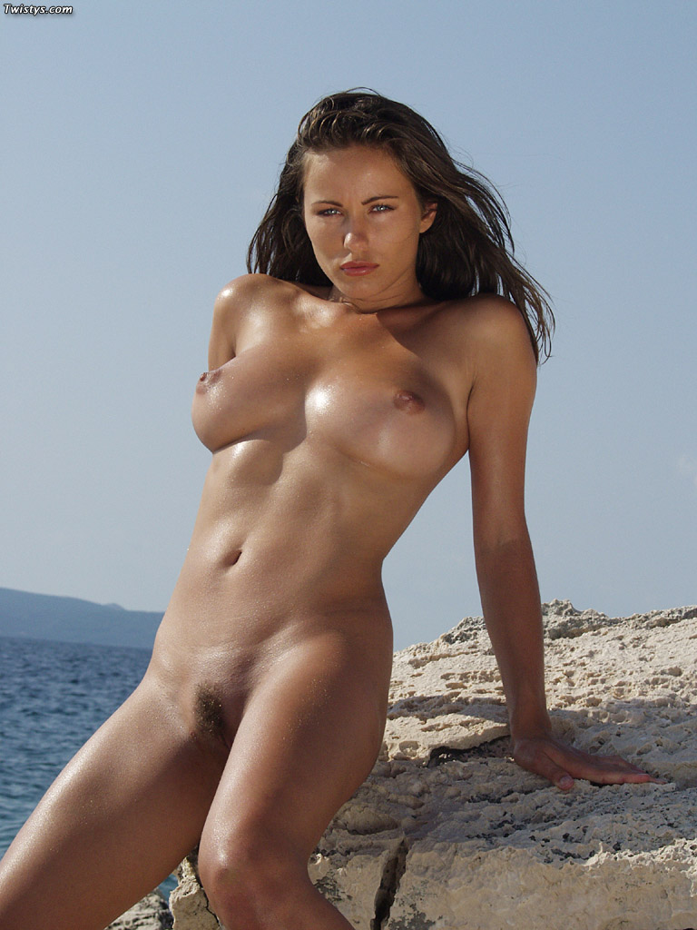 Fotos de una hermosa morena de ojos azules desnuda en la playa