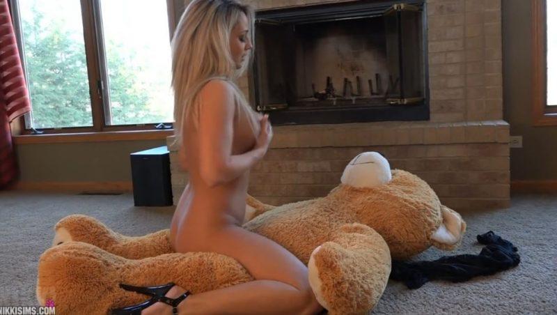 Chica rubia follando con un oso de peluche gigante
